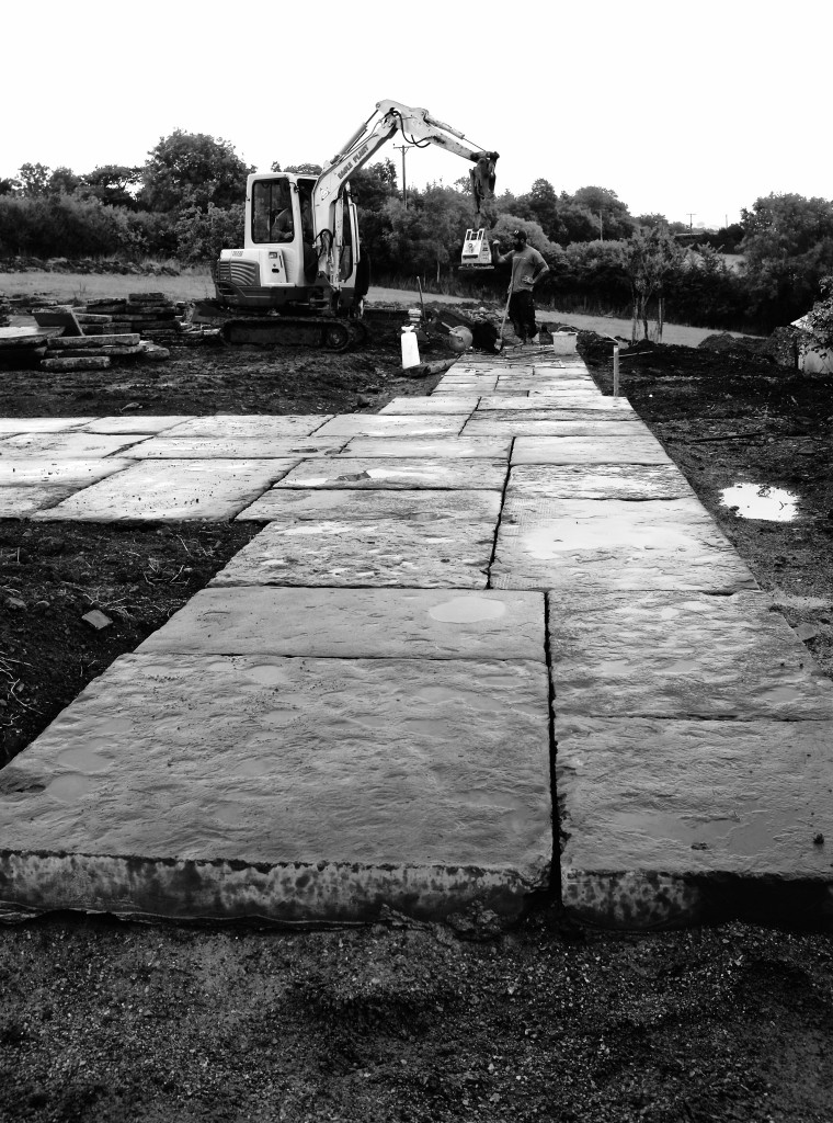 Devon country garden, reclaimed yorkstone path being dry laid.
